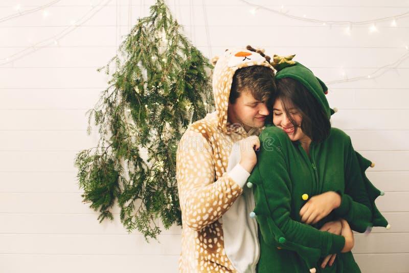 Счастливая пара в праздничных пижамах, обнимающаяся на свете рождественских деревьев в стильной комнате Празднование Рождества ил стоковое изображение rf