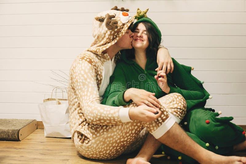 Счастливая пара в праздничных пижамах целуется на рождественские подарки, сидя на полу Празднование Рождества или Нового года Оле стоковые фотографии rf