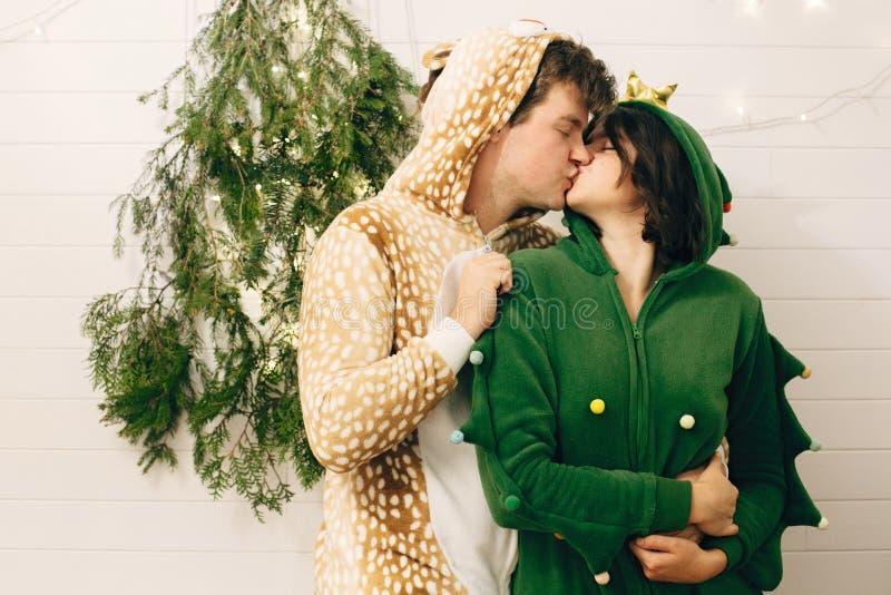Счастливая пара в праздничных пижамах целуется на свете рождественских деревьев в стильной комнате Празднование Рождества или Нов стоковое изображение rf