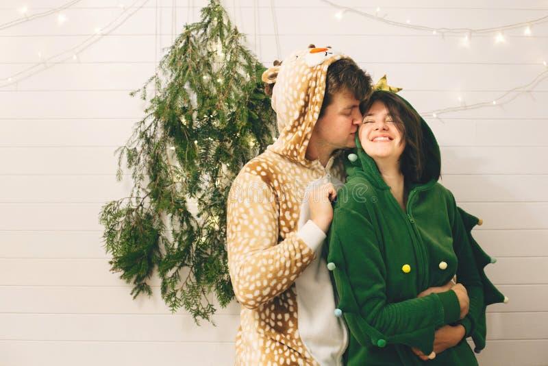 Счастливая пара в праздничных пижамах целуется на свете рождественских деревьев в стильной комнате Празднование Рождества или Нов стоковая фотография rf