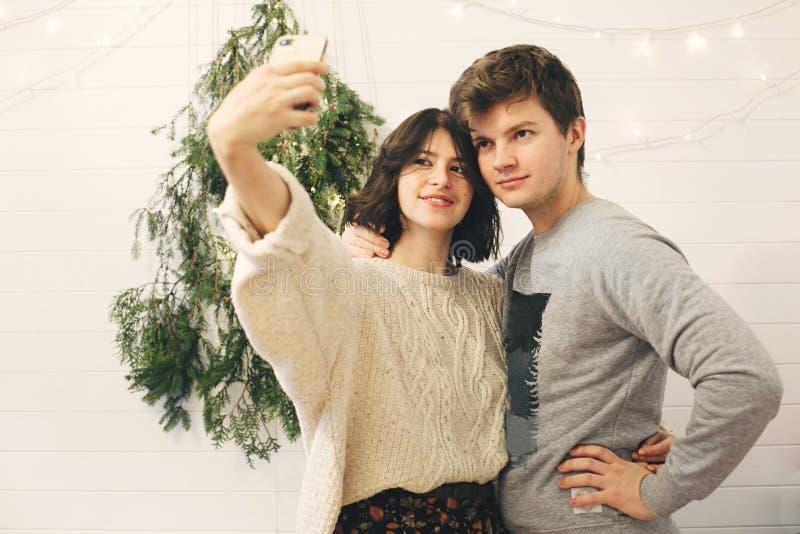 Счастливая пара хипстеров, которые занимаются селфи на современном свете рождественских деревьев в стильной праздничной комнате П стоковые фото