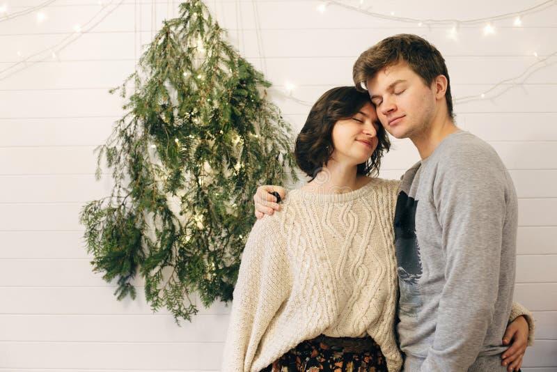 счастливая пара хипстеров нежно обнимается на современном свете christmas tree light в стильной праздничной комнате Празднование  стоковое изображение rf