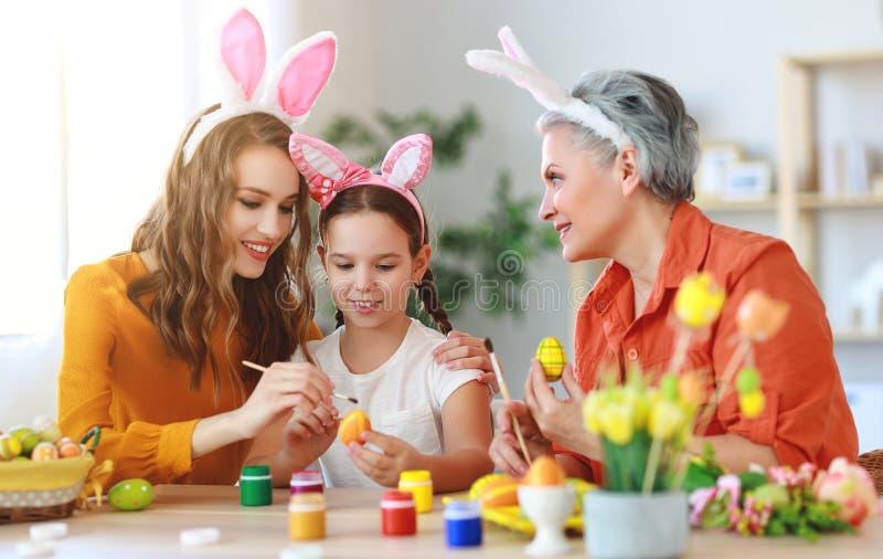 Счастливая пасха! бабушка, мать и ребенок семьи красят яйца и подготавливают на праздник стоковое изображение
