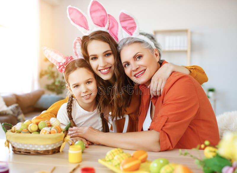 Счастливая пасха! бабушка, мать и ребенок семьи красят яйца и подготавливают на праздник стоковые изображения rf