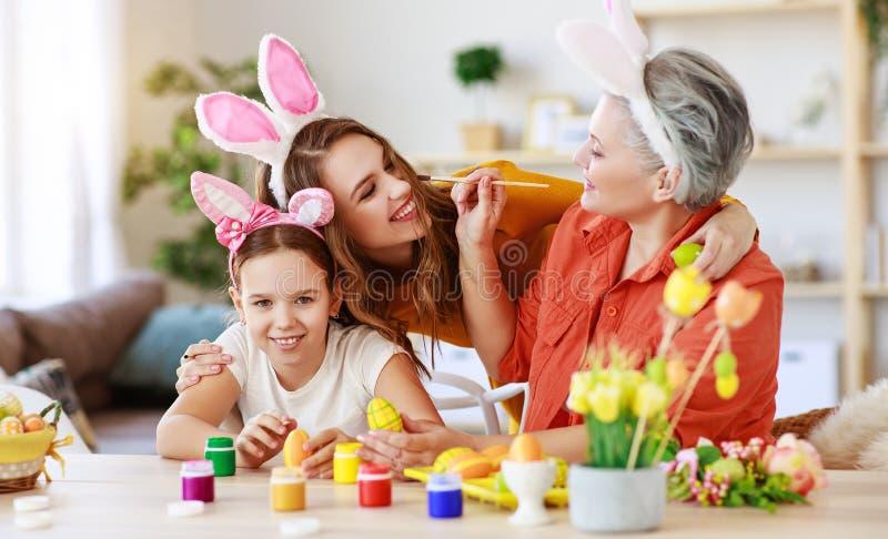 Счастливая пасха! бабушка, мать и ребенок семьи красят яйца и подготавливают на праздник стоковые изображения