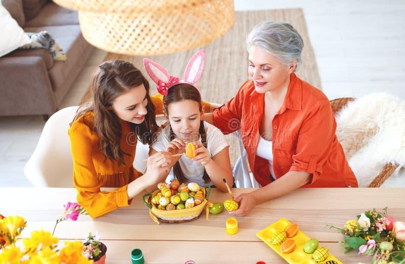 Счастливая пасха! бабушка, мать и ребенок семьи красят яйца и подготавливают на праздник стоковое изображение rf