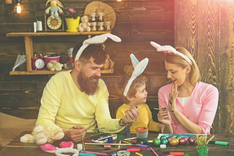 Счастливая пасха! Мать, отец и ребенок наслаждаются покрасить пасхальные яйца стоковые фото