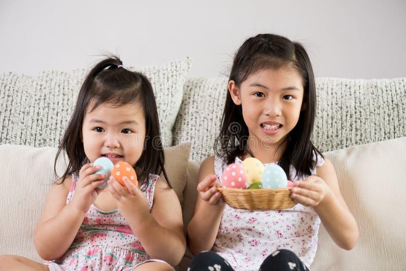 Счастливая пасха! 2 милых маленьких дет сидя на софе с пасхальными яйцами в гнезде или корзине стоковое изображение