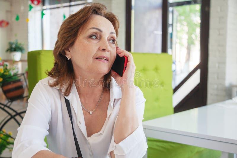 Счастливая пожилая белая женщина используя мобильное устройство сидя на кофейне стоковая фотография