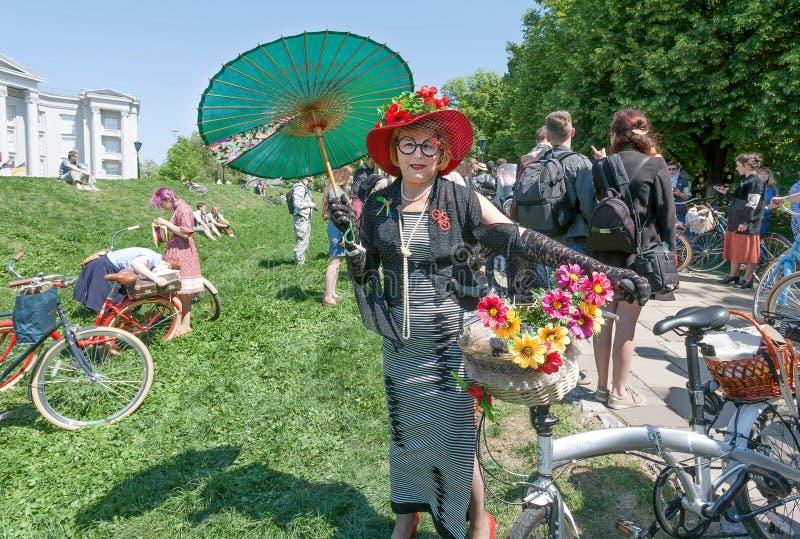 Счастливая пожилая женщина в старой моде одевает при велосипед представляя круиз внешнего фестиваля ретро стоковое фото