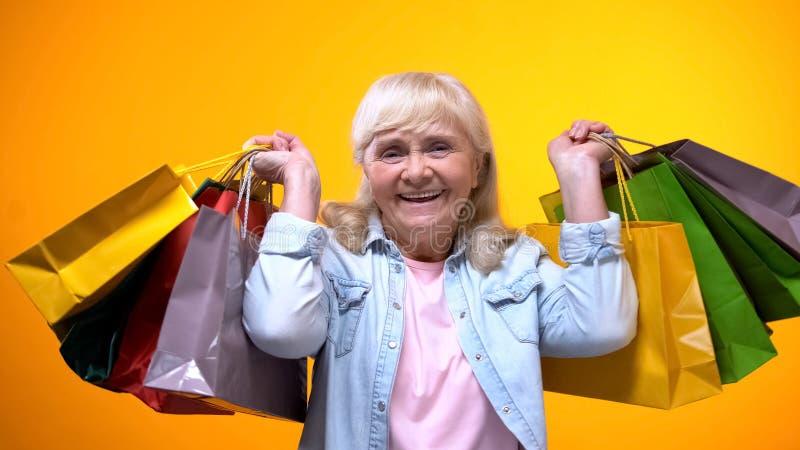 Счастливая пожилая женщина показывая много хозяйственных сумок, часы досуга, деньги траты стоковые изображения rf