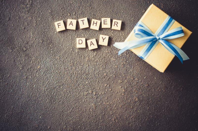 Счастливая поздравительная открытка Дня отца с украшенной подарочной коробкой на темной предпосылке стоковое фото