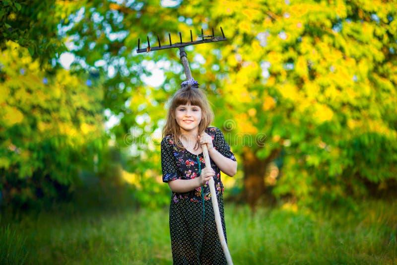 Счастливая помощь маленькой девочки parents в саде с грабл стоковые фотографии rf