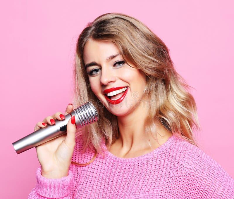 Счастливая поя девушка Женщина красоты нося розовый пуловер с mic стоковые изображения rf