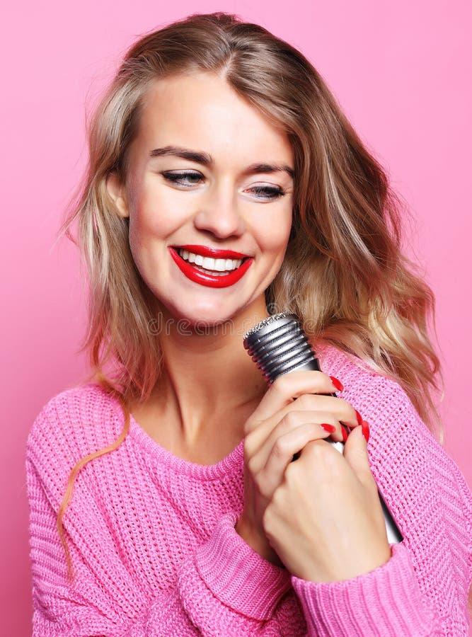 Счастливая поя девушка Женщина красоты нося розовый пуловер с mic стоковые изображения