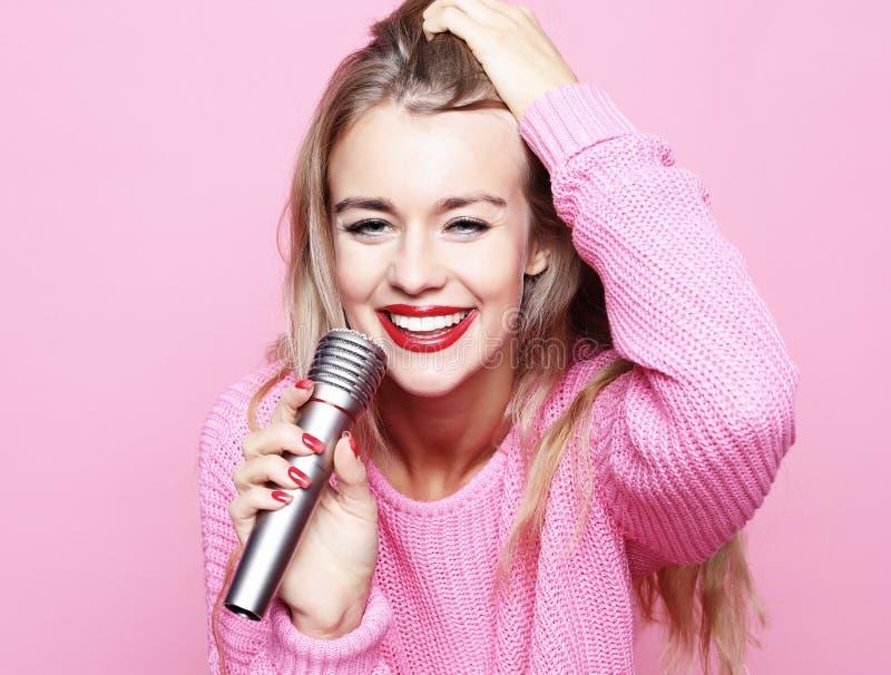 Счастливая поя девушка Женщина красоты нося розовый пуловер с mic стоковое изображение rf