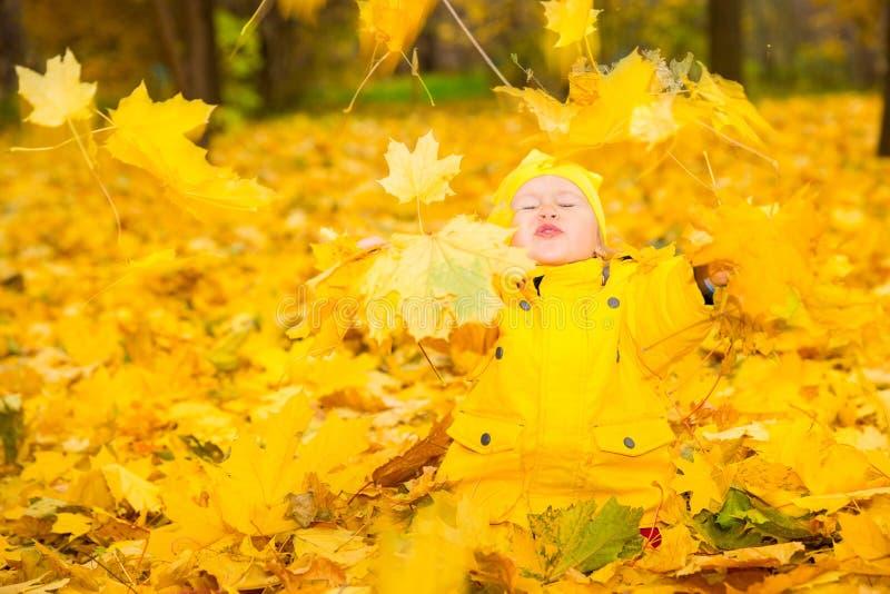 Счастливая прелестная девушка ребенка с листьями в парке осени падение офис bucharest c e стоковое изображение
