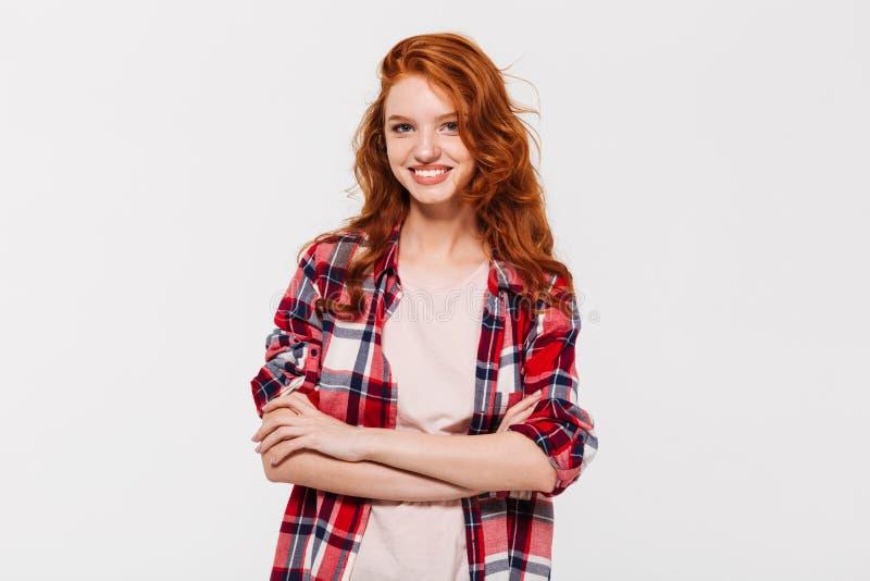 Счастливая привлекательная молодая дама redhead при пересеченные оружия смотреть камеру стоковые фотографии rf