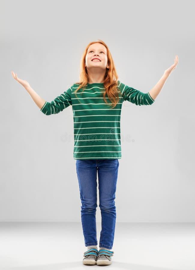 Счастливая признательная красная с волосами девушка смотря вверх выше стоковые изображения rf