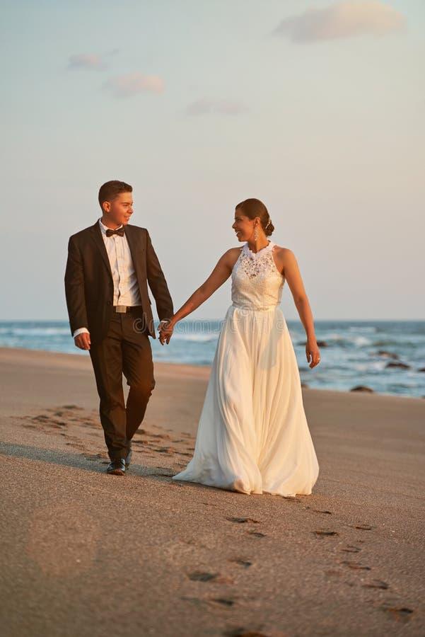 Счастливая прогулка groom и невесты на пляже стоковые фотографии rf