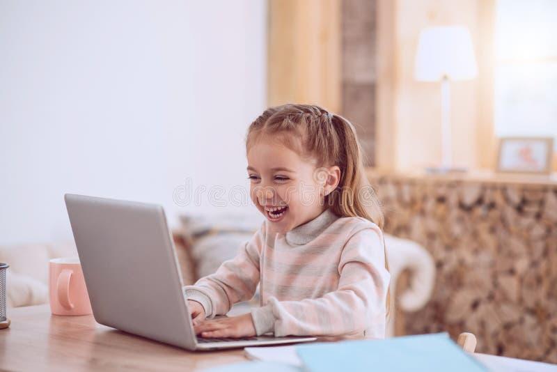 Счастливая радостная девушка играя на компьтер-книжке стоковые фото