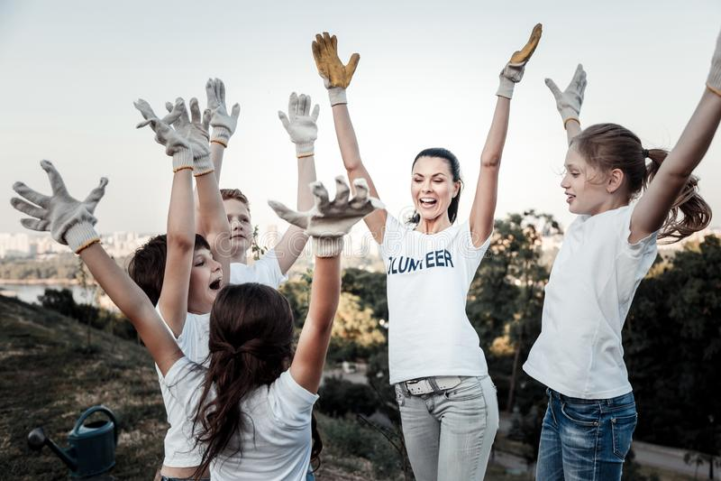 Счастливая радостная команда поднимая их руки стоковые изображения