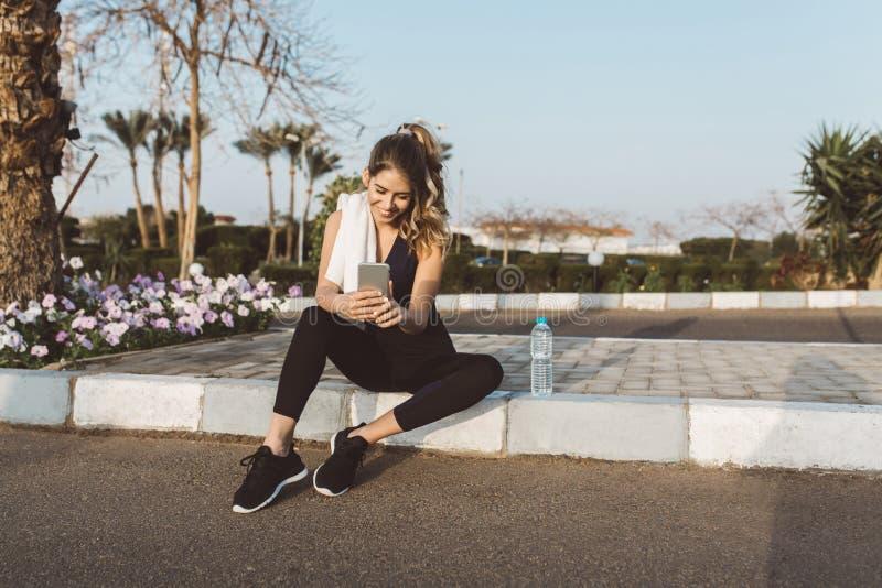 Счастливая радостная молодая женщина в sportswear сидя снаружи на улице тропического города Беседующ по телефону, выражая стоковая фотография rf