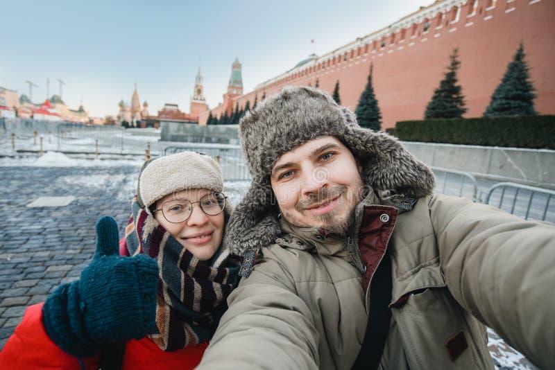 Счастливая романтичная пара туристов в зиме в теплых одеждах и шляпах делает selfie автопортрета перед Кремлем на красном цвете стоковое изображение