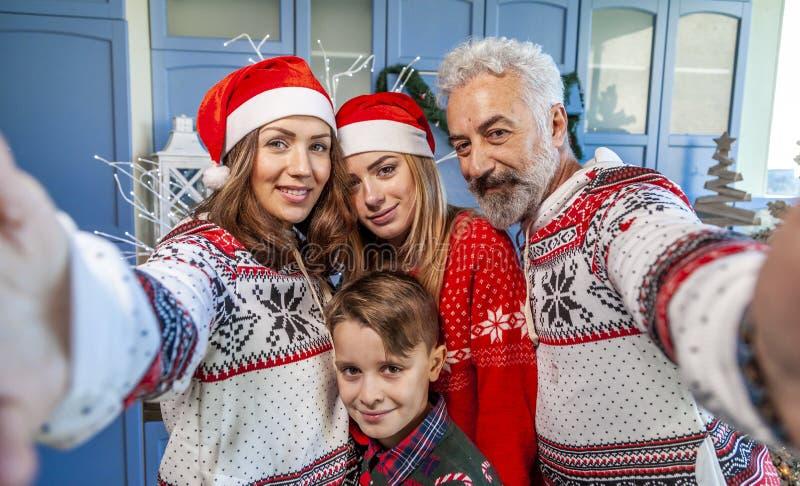 Счастливая семья воссоединенная на Рождество принимая selfie стоковые изображения rf