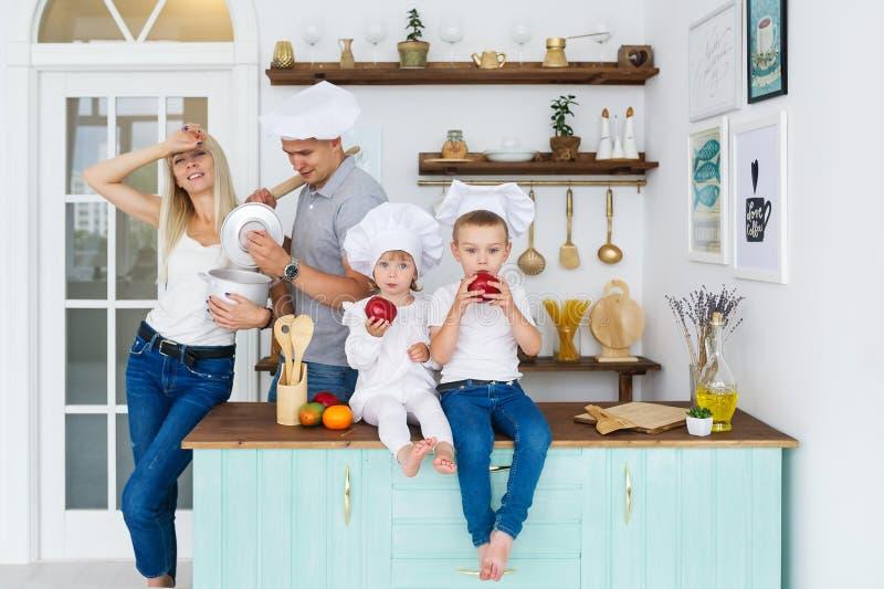 Счастливая семья в белых крышках при 2 дет варя дома еду стоковая фотография