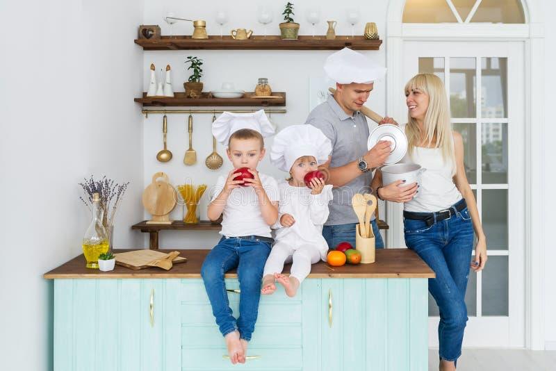 Счастливая семья в крышках кашевара с 2 детьми в домашней кухне стоковые фотографии rf