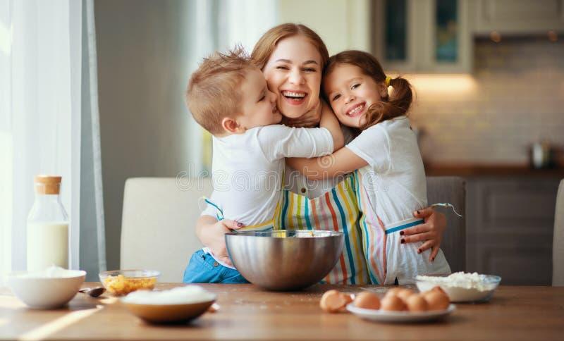 Счастливая семья в кухне мать и дети подготавливая тесто, пекут печенья стоковое фото rf