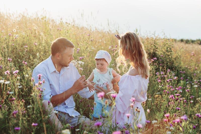 Счастливая семья в луге цветков стоковая фотография rf