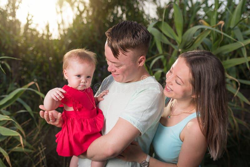 Счастливая семья в парке выравнивая свет Света солнца Прогулка мамы, папы и младенца счастливая на заходе солнца стоковые фото