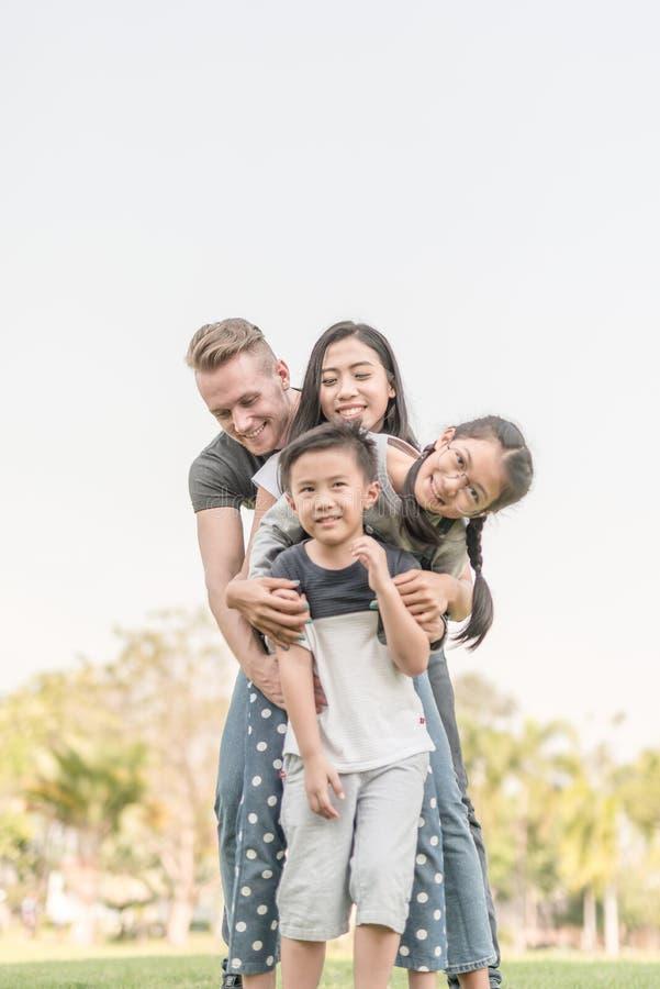 Счастливая семья в парке совместно на солнечный день стоковое изображение rf