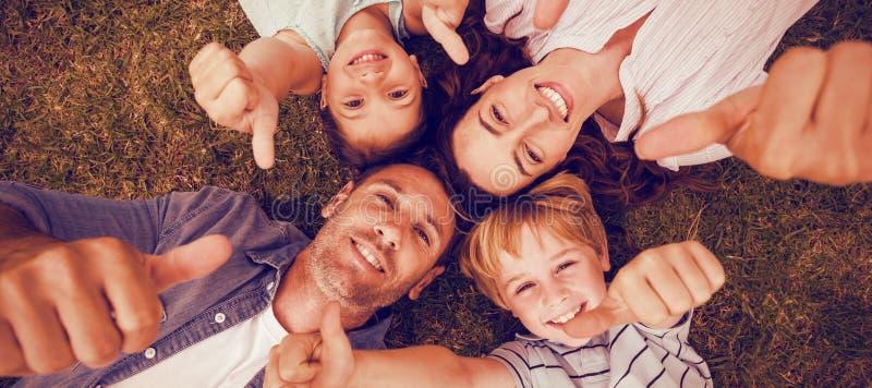 Счастливая семья в парке совместно показывать большие пальцы руки вверх стоковая фотография rf