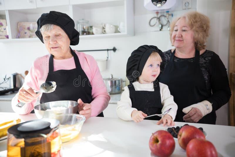 Счастливая семья делая блинчик в кухне Яблоки на таблице стоковые фотографии rf