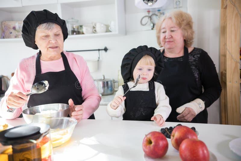 Счастливая семья делая блинчик в кухне стоковое фото