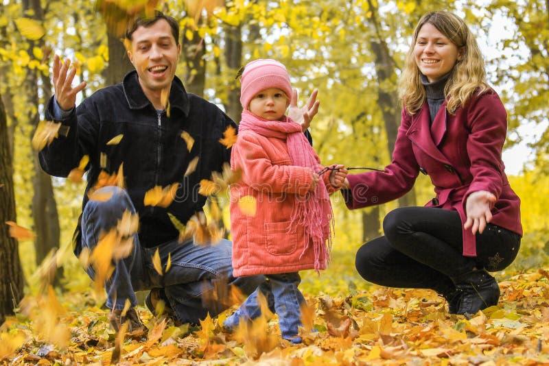 Счастливая семья играя в листьях осени в парке на природе стоковые фото