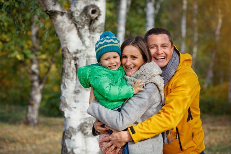 Счастливая семья играя в парке осени стоковое изображение rf