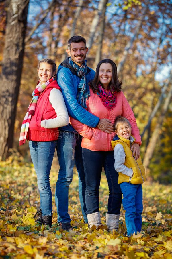Счастливая семья играя в парке осени стоковое изображение