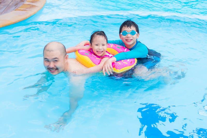 Счастливая семья играя в плавательном бассеине стоковые изображения