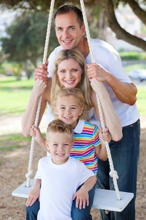 Счастливая семья играя на качании стоковые изображения