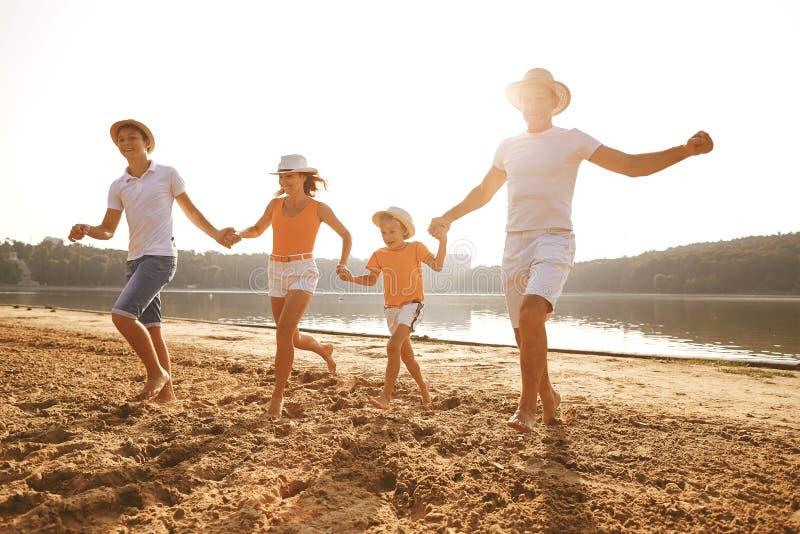 Счастливая семья играя на пляже на заходе солнца стоковое фото rf