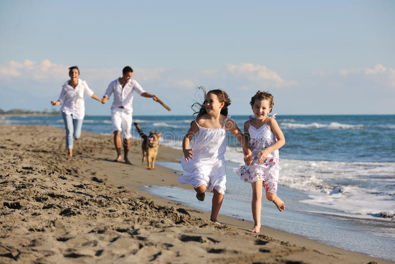Счастливая семья играя с собакой на пляже стоковое фото rf