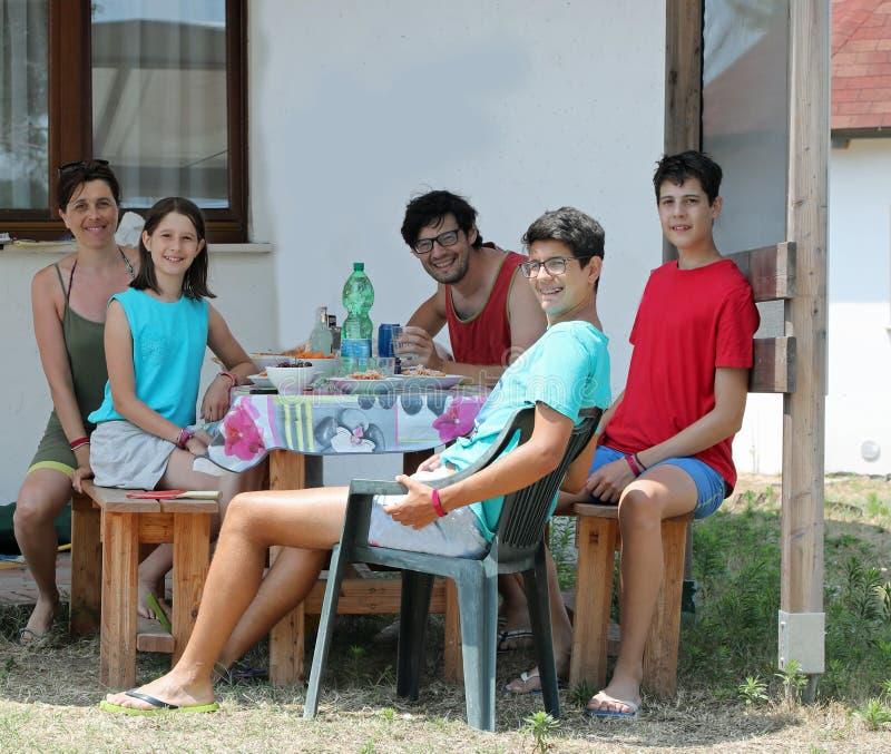 Счастливая семья из пяти человек с тремя детьми за пределами бунгало t стоковое изображение rf