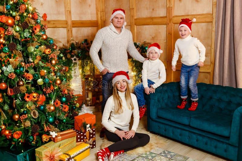 Счастливая семья из четырех человек в связанных свитерах для рождества стоковые фотографии rf