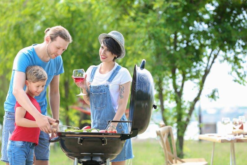Счастливая семья имея барбекю с современным грилем стоковое изображение rf