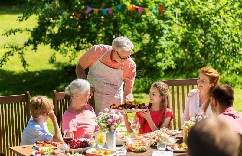 Счастливая семья имея обедающий или прием гостей в саду лета стоковые фотографии rf