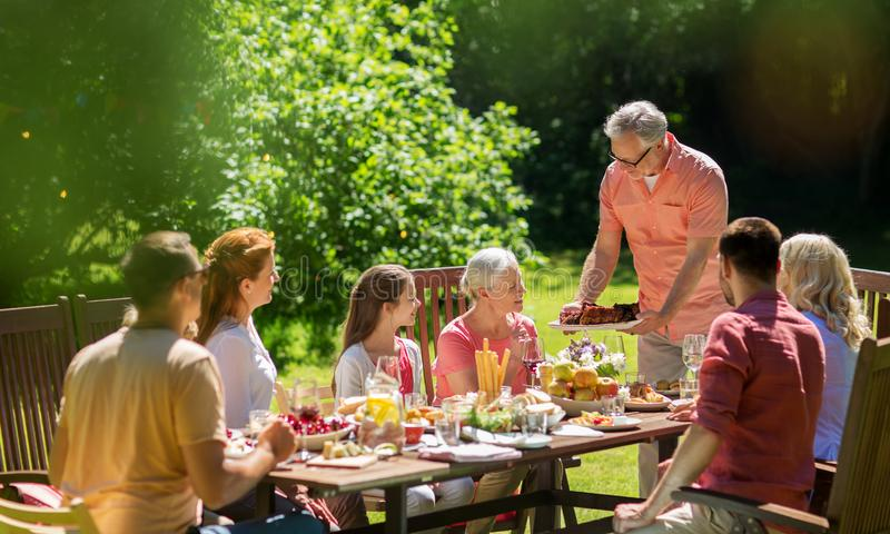 Счастливая семья имея обедающий или прием гостей в саду лета стоковая фотография